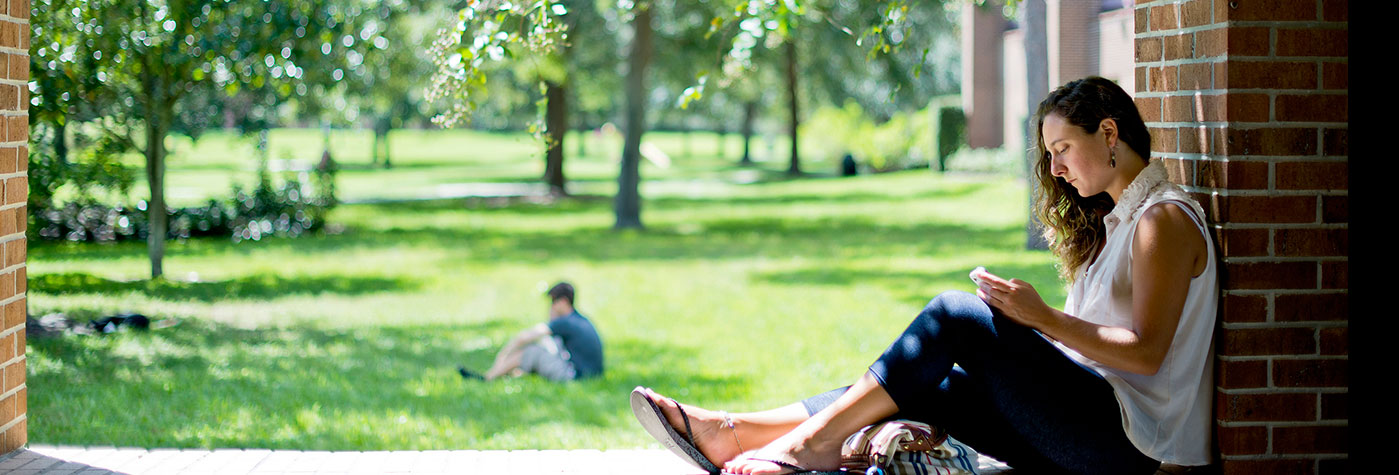 A student sitting outside the UCF John T Washington Center